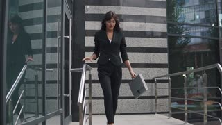attractive business woman exits from a modern business center and confidently walks down the street