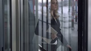 Attractive business woman walking on office building. SLOW MOTION