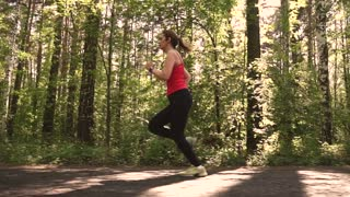attractive girl goes in for sports in the woods. young woman Jogging in the Park at sunset. slow motion