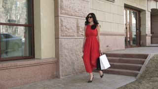 attractive girl happily walks down the street with shopping bags. Young woman in a red dress smiles after a successful shopping. Slow motion