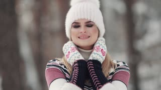 attractive girl in winter forest touches mittens to face