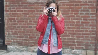 Attractive young girl takes photos on a film camera