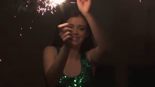 attractive young woman having fun and dancing at the party with sparklers