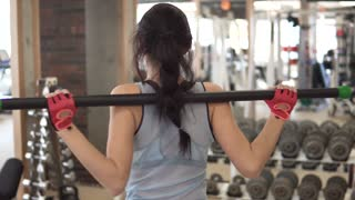 attractive young woman warming up before a workout in the gym