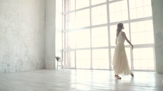 ballerina dances in a white light dress. ballet dancer in pointe shoes. ease and grace. slow motion
