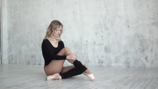 ballerina spreads leggings sitting on the floor in pointe shoes