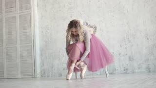 ballerina tying the pointes. ballet dancer wearing ballet shoes in the studio
