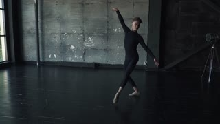 ballet dancer makes a high jump and pirouette. young man dancing against a dark background in the studio. slow motion