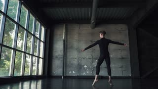 ballet dancer. young man gracefully dancing on a dark background in the studio. slow motion