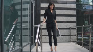 beautiful business woman in a strict suit and with a folder for papers goes near the business center