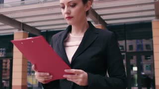 Beautiful confident young business woman is in a hurry to negotiate and looks at the clock. Girl in business clothes with a red folder in hands on the background of an office building