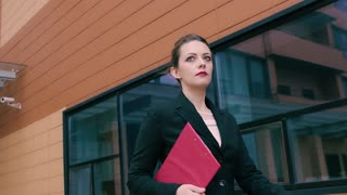 Beautiful confident young business woman is in a hurry to negotiate. Girl in business clothes with a red folder in hands on the background of an office building. SLOW MOTION