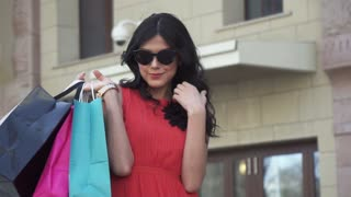 beautiful girl enjoys shopping. The brunette holds in hands shopping bags. shopaholic in a red dress and sunglasses. slow motion