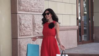 Beautiful girl in a red dress and sunglasses walking down the street with shopping bags. The brunette is happy with successful shopping, she smiles and rejoices. SLOW MOTION