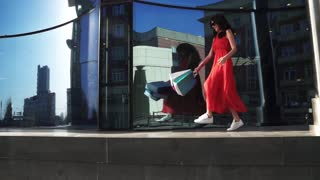Beautiful girl in a red dress is reflected in shop windows. Brunette with bags for shopping in hands. SLOW MOTION