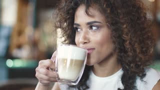 Beautiful hispanic woman enjoys the latte in a cozy cafe