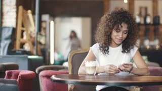 beautiful hispanic woman messaging on smartphone and smiling sincerely. young girl mulatto drinks coffee in a cafe