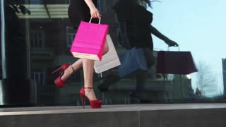 Beautiful legs in shoes with heels go along the glass shop window. Sexy legs close-up. beautiful young girl in red dress with shopping bags in hand enjoying the beautiful weather. SLOW MOTION