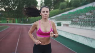 beautiful runner Jogging on the track in the stadium. slow motion