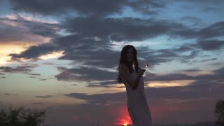 beautiful sexy girl in vecherom dress dancing on the beach at sunset. a young woman holds the sparklers and have fun at the party. slow motion