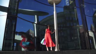 Beautiful young girl in the shop window. The brunette in a red dress and sunglasses is holding shopping bags. Professional european model posing on camera. SLOW MOTION