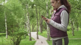 beautiful young girl turns on the music and starts jogging. The sportswoman listens to the music in training. slow motion