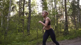 Beautiful young woman doing sports in nature. Athletic girl on a run. slow motion