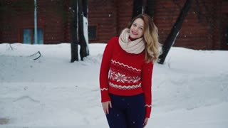 beautiful young woman in sweater on the street in winter looking and smiling at camera.
