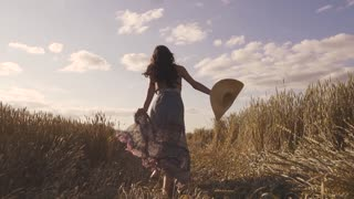beautiful young woman running across the field with a straw hat turns around smiling at the camera. slow motion