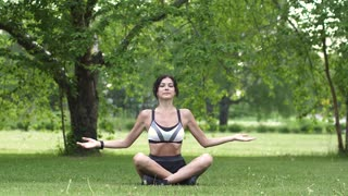 Beautiful young woman with smart watch in sportswear practicing yoga outdoors. 20s girl is doing breathing exercises at dawn on the park