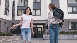 best friends are walking around the city. girlfriends laugh and fool around while walking down the street. girls enjoy the beautiful weather on the walk. slow motion