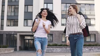 best friends laugh and fool around while walking down the street. girls enjoy the beautiful weather on the walk. slow motion