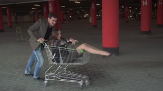 Best friends spend time together and have fun. A young man is rolling his girl on a trolley in a parking lot. young people enjoying outdoors with shopping trolley race. slow motion