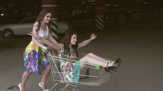 best friends spend time together and have fun. friend racing grocery carts in the Parking lot. young people enjoying outdoors with shopping trolley race. slow motion