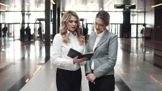business meeting of two business women in the lobby of an office building