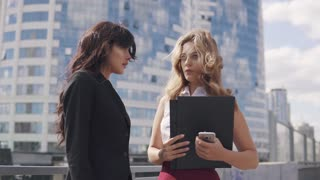business partners talk on the go. two business women in formal suits on the background of the business center
