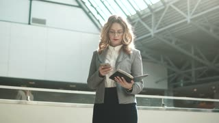 business woman in gray jacket sends message from mobile phone and looks at smart watch