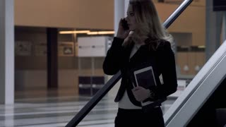 business woman talking mobile phone in modern office building