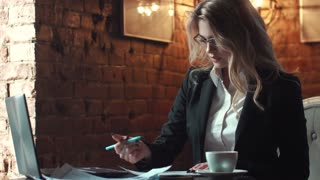 business woman working with documents in the office in the strength of a loft. a girl in business clothes and wearing glasses. business make-up and hairstyle