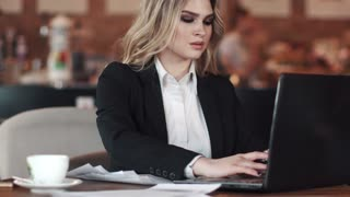 business woman working with documents sitting at a table in a coffee shop. girl in jacket and blouse. business makeup and hairstyle