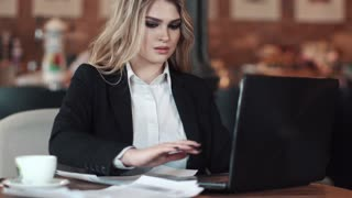 business woman working with documents sitting in a cozy coffee shop