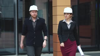 businessman and his female colleague on a construction site. the architects in the construction hard hats inspect a building. attractive girl holds the plan in his hands businesswomans at work