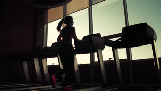 cardio on the treadmill. exercises for weight loss. silhouette of a girl on a treadmill. young sporty girl running on the treadmill at the gym. athlete in sportswear