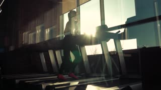 cardio workout in the gym. silhouette of a girl on a treadmill. young sporty girl running on the treadmill at the gym. athlete in sportswear