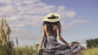 carefree girl running across the field looks around and smiles at the camera. Portrait of a young woman in a straw hat and rustic clothes. slow motion