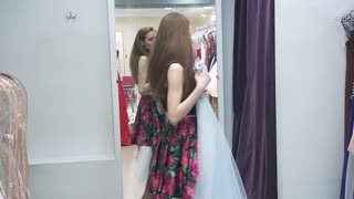 Charming girl trying on a dress