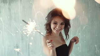 cheerful girl enjoys dancing and holding sparklers. the girl at the party. young woman on celebration. the festive mood. slow motion