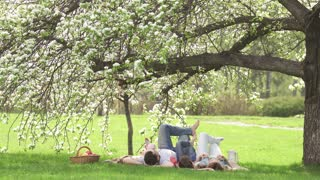 Cheerful portrait of a young family. Parents with their children lie under a blossoming apple tree. Family having fun on picnic
