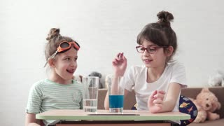 chemical experiment. children are engaged in elementary chemistry at home. the elder sister explains the basics of science to the younger sister. children's science