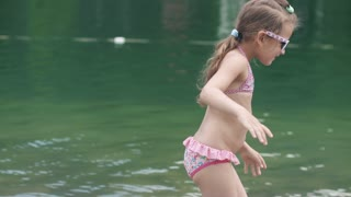 child bathing in the river and making funny faces. little girl in swimsuit and sun glasses enjoying a day by the sea. Slow motion